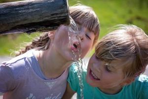 Kinder beim Trinken von Quellwasser